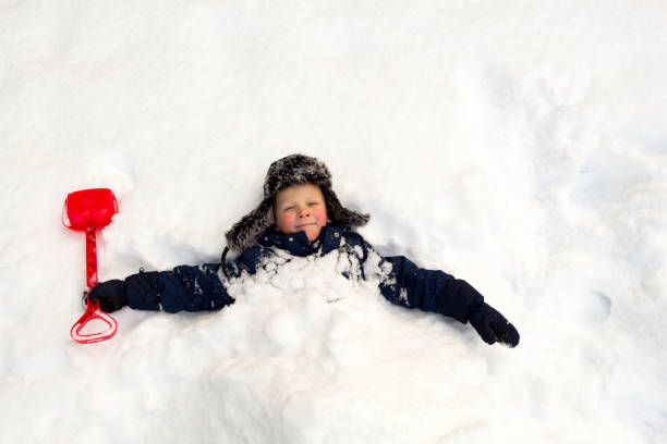The child buried himself with a children's shovel around the neck in the snow stock photo