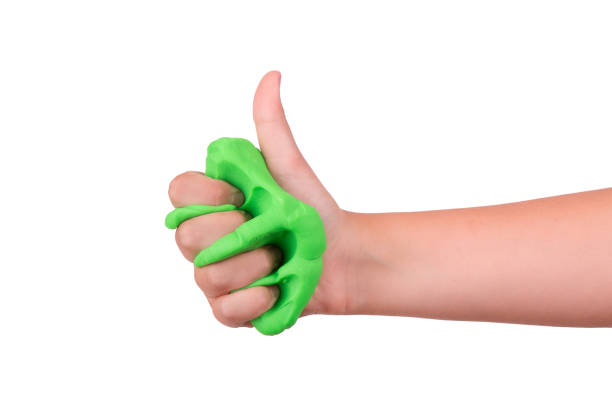 The child crushes the slime in his hand. Slime sandwiched in hand. The game is green slime. Slime in the hand of a child. slimy stock pictures, royalty-free photos & images