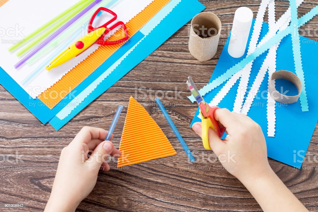 The child cuts out the details of a paper boat, congratulations...
