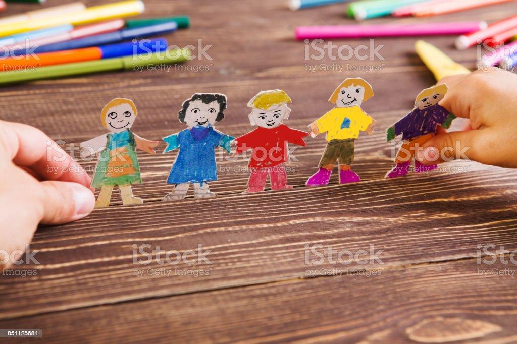 das Kind hat Zahlen von Menschen aus Papier. Papier-Menschen auf hölzernen Hintergrund. Kreative Kinderspiel mit Handwerk. - Lizenzfrei Bastelarbeit Stock-Foto