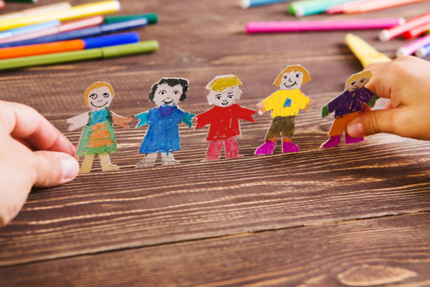 the child does figures of people of paper. Paper people on wooden background. Creative child play with craft. stock photo