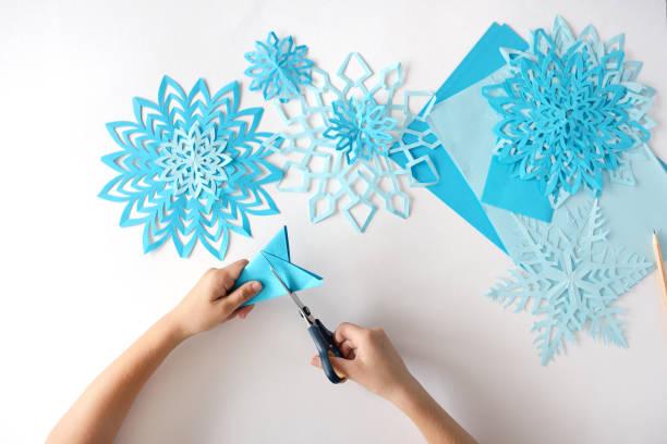 das kind tut schneeflocken von blauem papier. - winterdeko basteln stock-fotos und bilder
