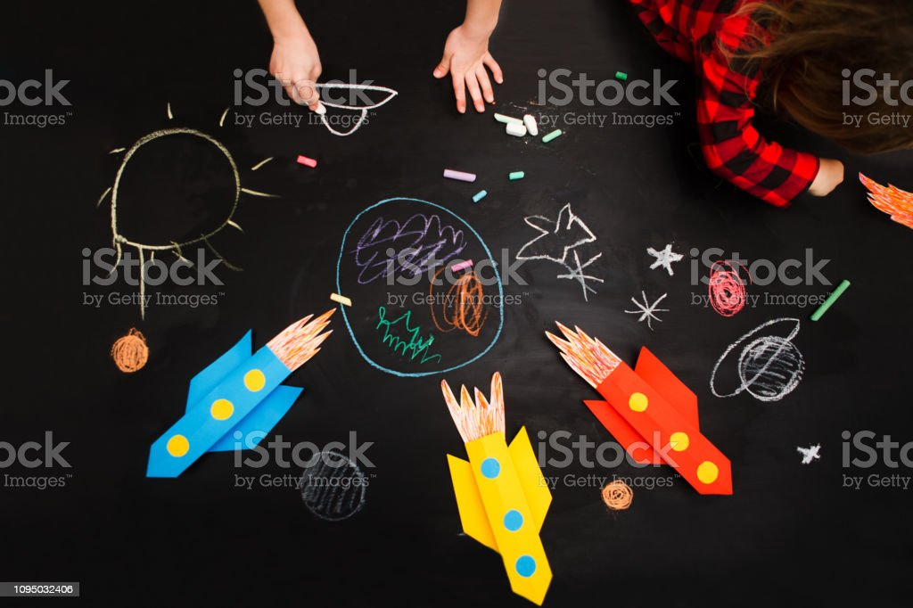 the child draws a rocket and space on a blackboard. preschool Child...