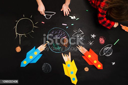 istock the child draws a rocket and space on a blackboard. preschool Child in creativity in the home. 1095032406