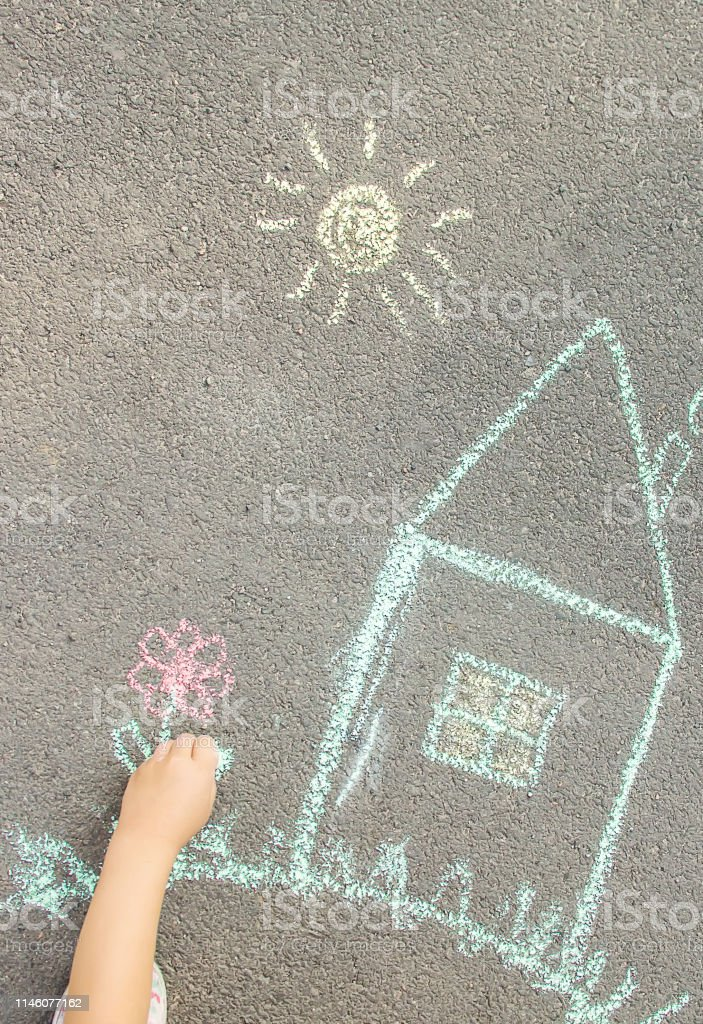 The child draws the house with chalk on the asphalt. Selective focus....