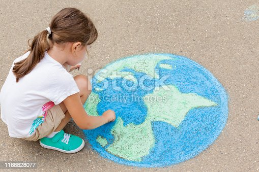 the  child girl draws a planet of the world with colored chalk on the asphalt. Children's drawings, paintings and concepts. Education and art, be creative when you return to school.  earth, Peace day