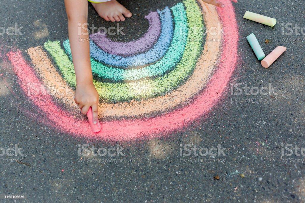 das Kind zieht einen Regenbogen mit farbiger Kreide auf den Asphalt. Kind Zeichnungen Gemälde Konzept. Bildung und Kunst, kreativ sein, wenn man wieder zur Schule zurückkehrt - Lizenzfrei Kind Stock-Foto