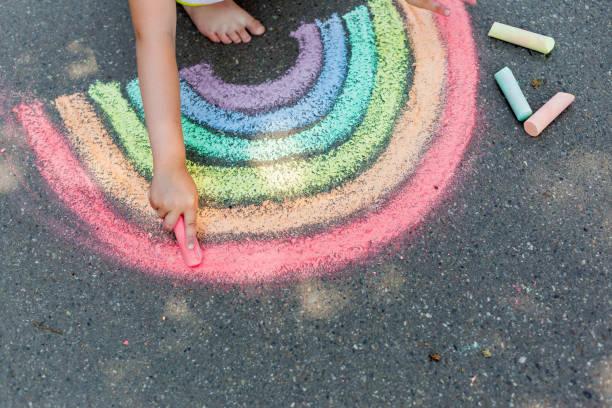 das kind zieht einen regenbogen mit farbiger kreide auf den asphalt. kind zeichnungen gemälde konzept. bildung und kunst, kreativ sein, wenn man wieder zur schule zurückkehrt - kreide stock-fotos und bilder