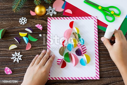 istock The child glues the parts Christmas tree greeting card. Handmade. Project of children's creativity, handicrafts, crafts for kids. 1034427294