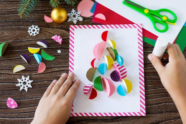 das kind klebt die teile weihnachtsbaum-grußkarte. handgefertigt. projekt von der kreativität der kinder, basteln, basteln für kinder. - winterdeko basteln stock-fotos und bilder