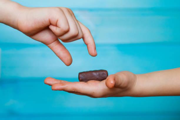 das kind hält eine praline in die innenfläche seiner hand mit seinem freund zu teilen - kinderschokolade stock-fotos und bilder
