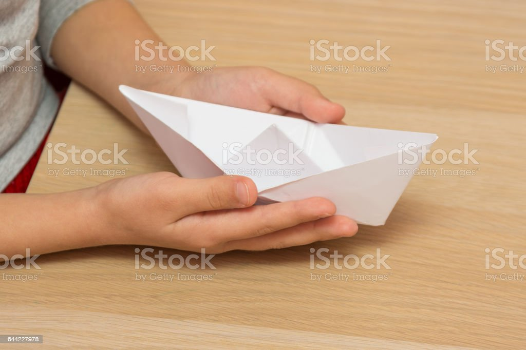 The child holds in his hands a paper boat, close-up