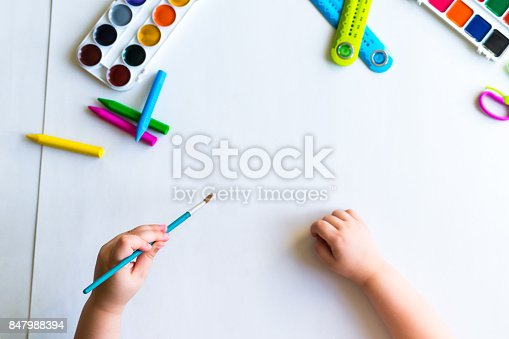 istock The child holds the brush over the sheet 847988394