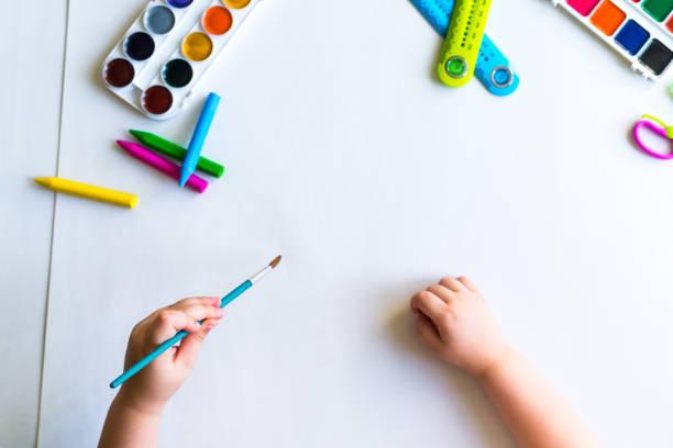 Das Kind hält den Pinsel über das Blatt – Foto