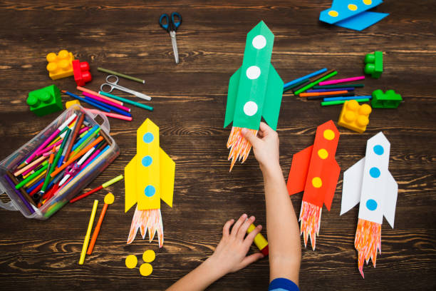 the child holds the rocket made of paper against the background of a wooden table. preschool Child in creativity in the home. Happy kid makes rockets from paper. Children's creativity. the child holds the rocket made of paper against the background of a wooden table. preschool Child in creativity in the home. Happy kid makes rockets from paper. Children's creativity. craft stock pictures, royalty-free photos & images
