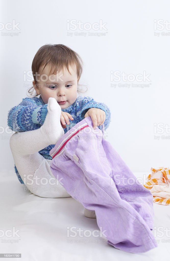 The child is dressing pants stock photo