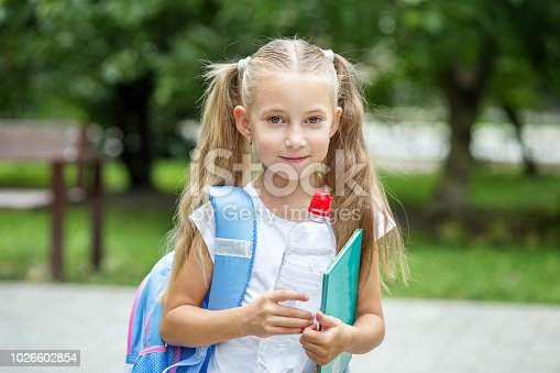 istock The child is holding a book and a bottle of water. The concept of school, study, education, friendship, childhood 1026602854