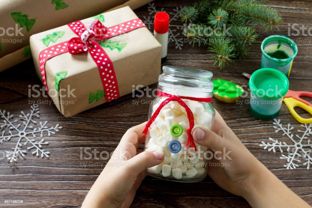 The child is making Christmas presents. Christmas gift box and...