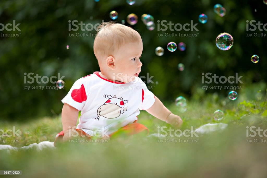 The child is sitting on the grass surrounded by soap bubbles stock photo