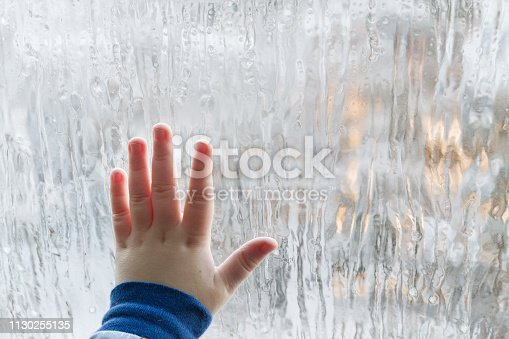 The child leaned his palm against the frosty winter window