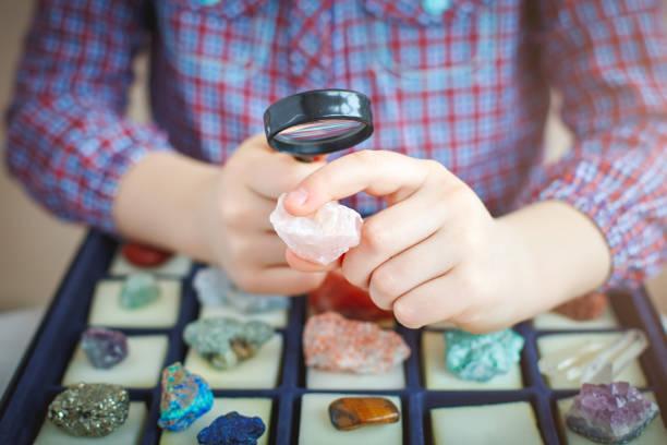 dziecko patrzy na swoją kolekcję minerałów. mały geolog. - geologia zdjęcia i obrazy z banku zdjęć