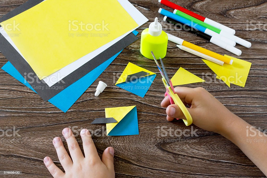 The child makes a book with a bookmark mignon. The child carves the...
