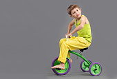 The child on a tricycle on a gray background. Funny little boy is playing.The boy rides a bicycle.