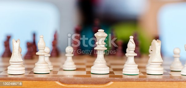 A child spending time playing chess. Chess figures close up with a moving hand.