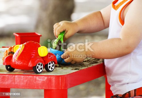 Playground. Children's outdoor games. The child plays with sand and plastic toys.