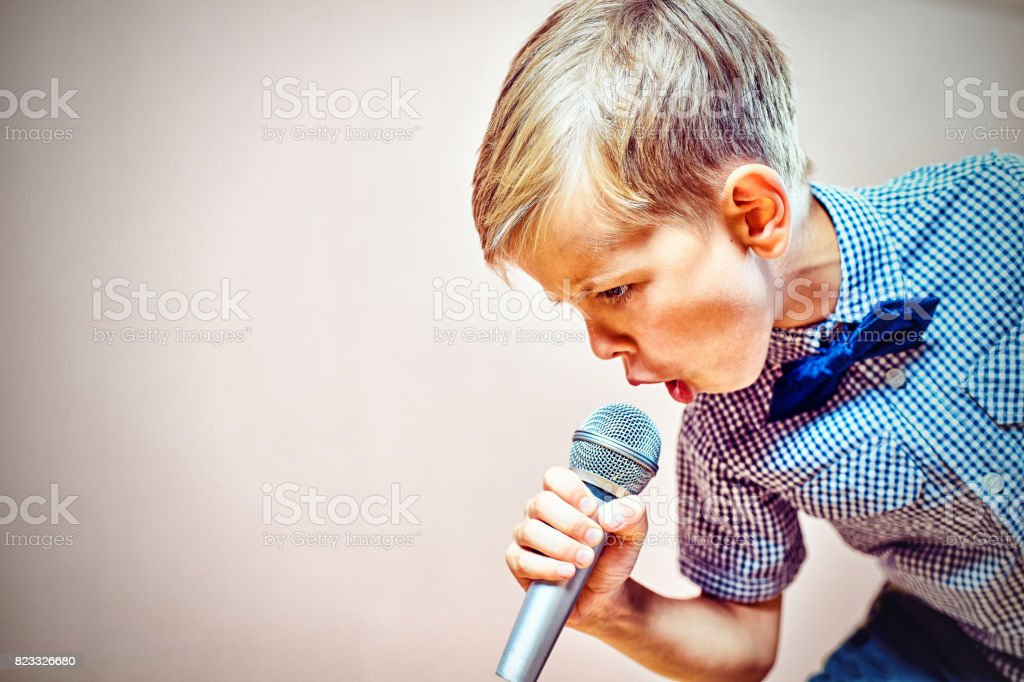 The child sings into the microphone stock photo