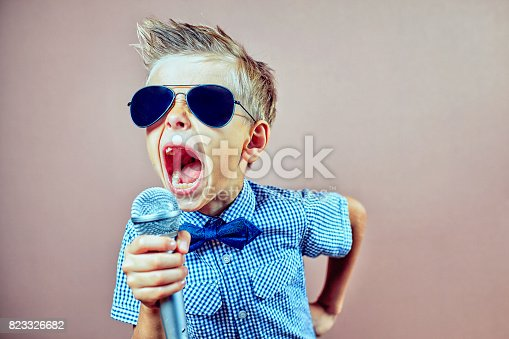istock The child sings into the microphone 823326682