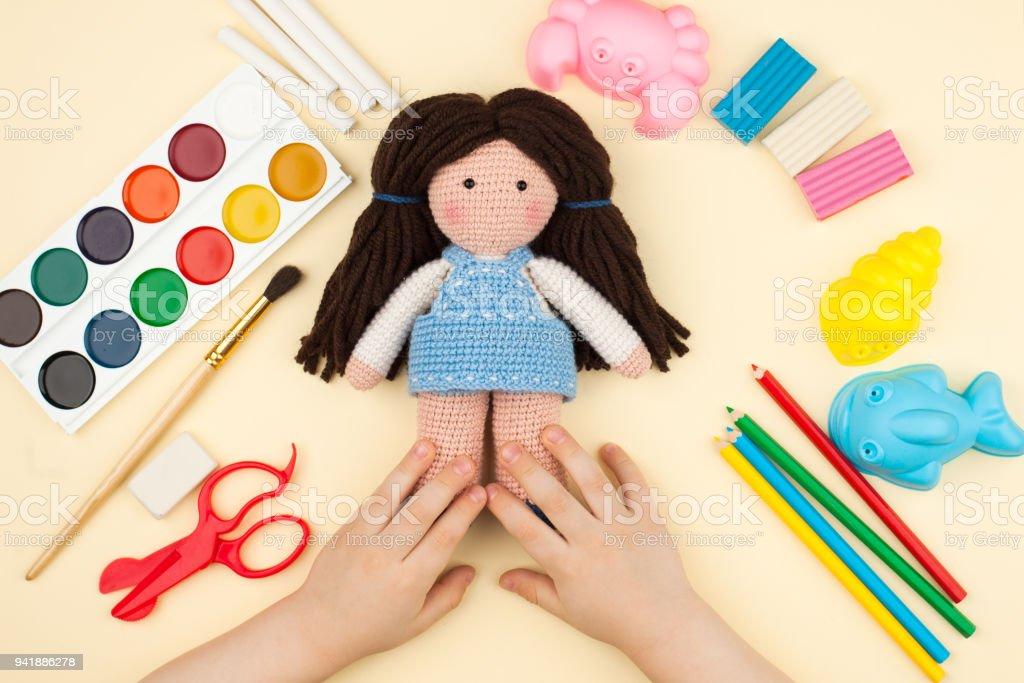 el niño se sienta a la mesa con objetos de dibujo, creatividad y ocio, es una muñeca de ganchillo en las manos, una vista superior - foto de stock
