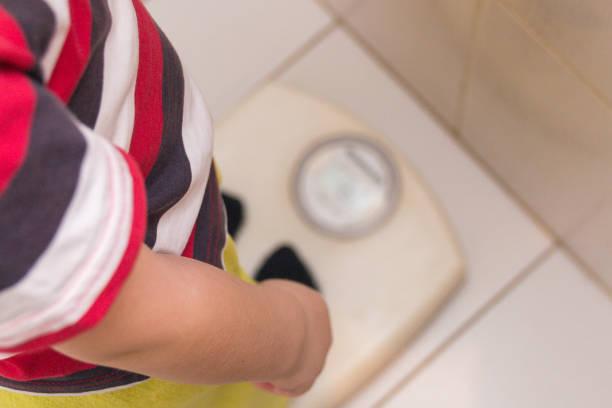a criança fica as balanças de chão com uma camisa listrada, a vista do topo. saúde - infância - fotografias e filmes do acervo