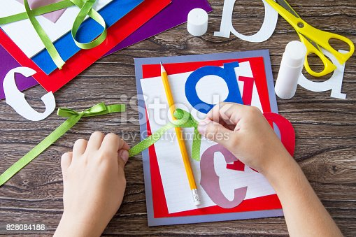 istock The child ties the tape of the ribbon details of the applique. Greeting card with a pencil and letters for the new school year. Children's Art Project, needlework, crafts for kids. 828084186