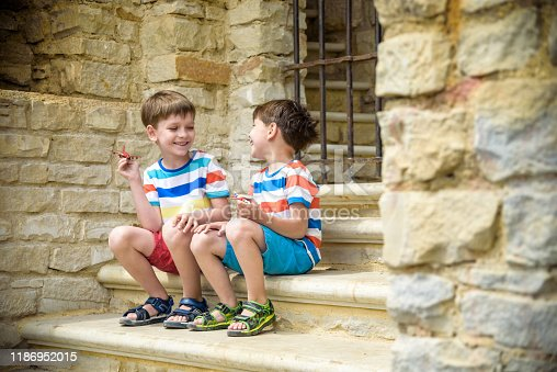 istock The children playing on the ruins of ancient building with metal gate an archaeological site of an ancient city. Two boys sitting and play with toy aircraft plane. Travel concept 1186952015