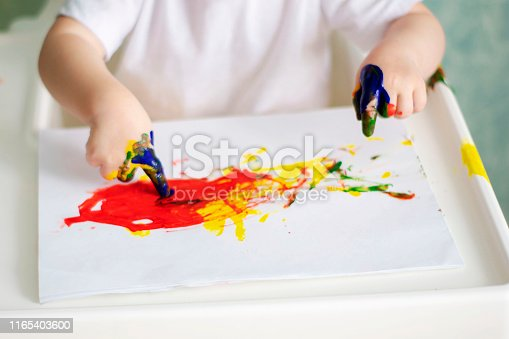 The children's palms, soiled with paint, amuse the child.