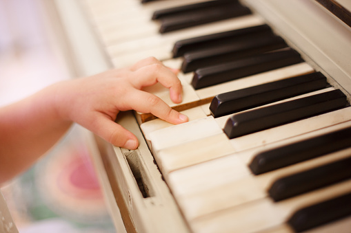 the child's hand plays the piano keys