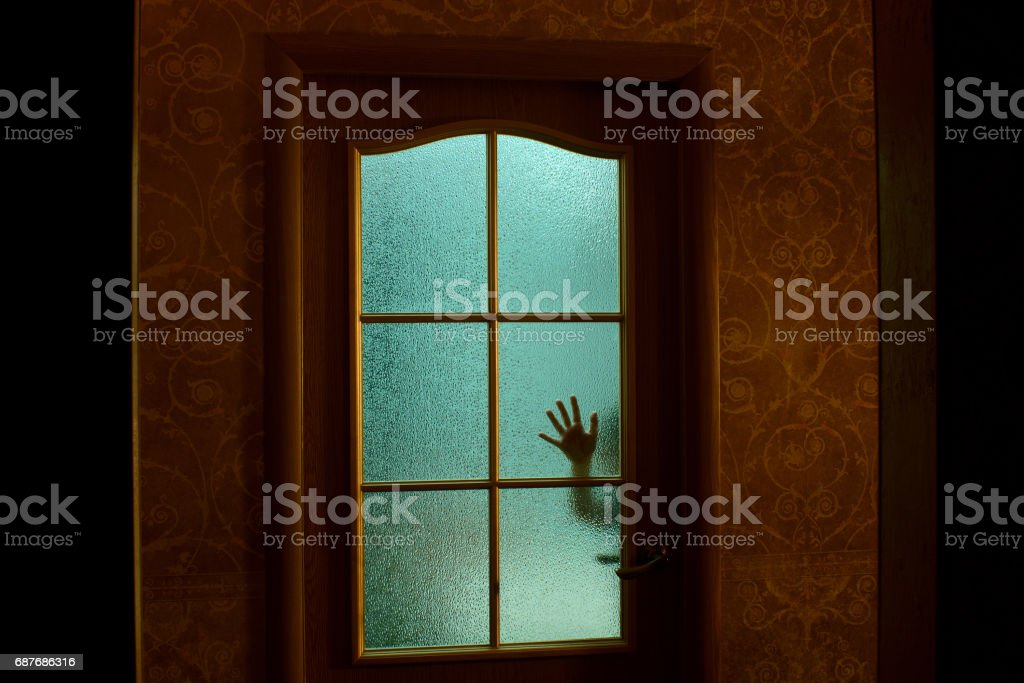 The child's hand through the glass door in the apartment. Green light from the room. Fear. stock photo