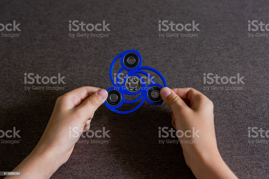 The child's hands hold the Spinner. A popular toy for concentration of attention, prevention of ADHD. Spinner. Kids toy stock photo