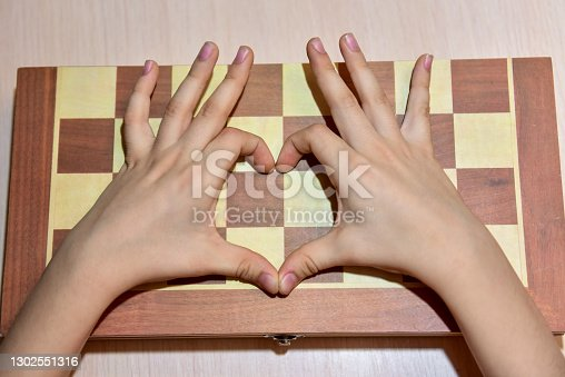 the child's hands on the chessboard show the heart and love of playing chess.