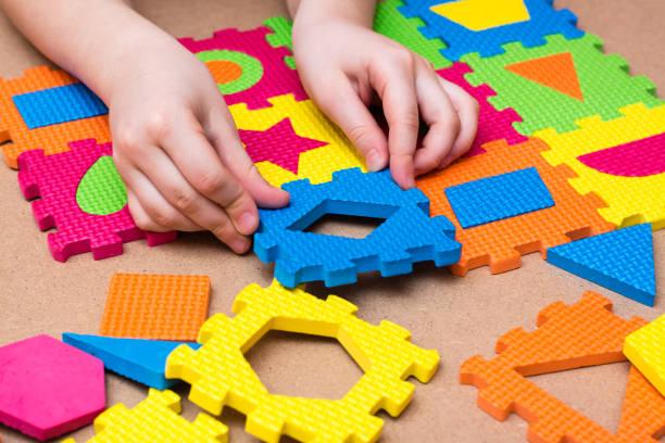 Çocuğun elleri tabloda farklı geometrik şekillerin ayrıntıları ile bir renk bulmaca öğe koymak. Çocuğun hapsedilmesi. Masa oyunu stok fotoğrafı