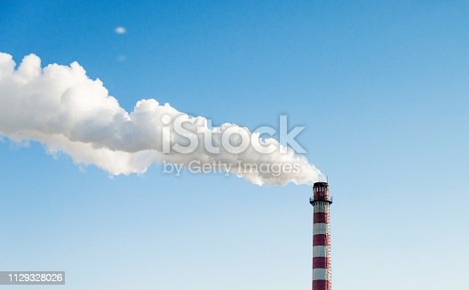 istock The chimney with smoke into the sky 1129328026
