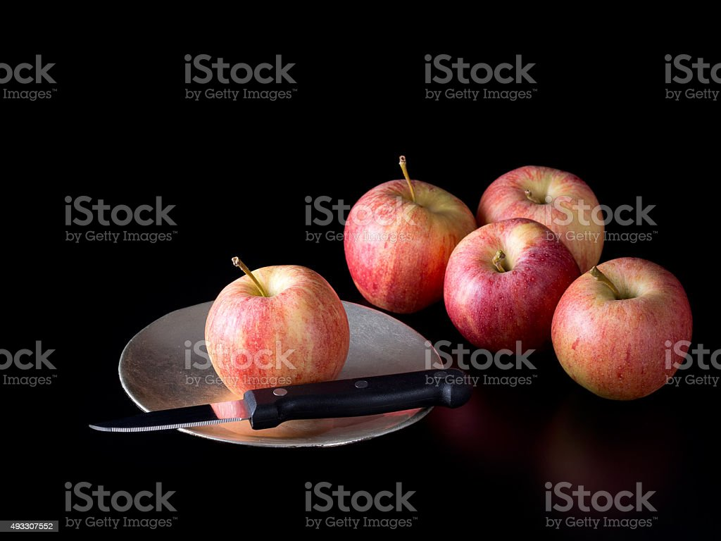 The chosen one. Apple with knife on plate. Dark background. stock photo