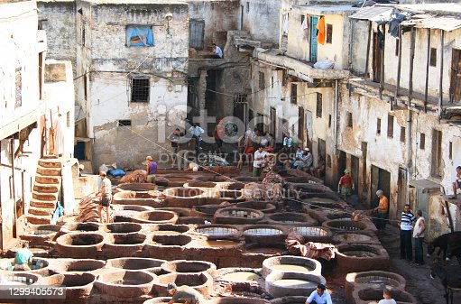 Fez, Morocco - July 29, 2013: Workers dying leather at the Chouara Tannery in the Fes el Bali medina quarter of Fez Morocco