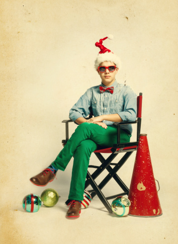 the christmas movie, teen siting on a film director chair, thinking about the plot.