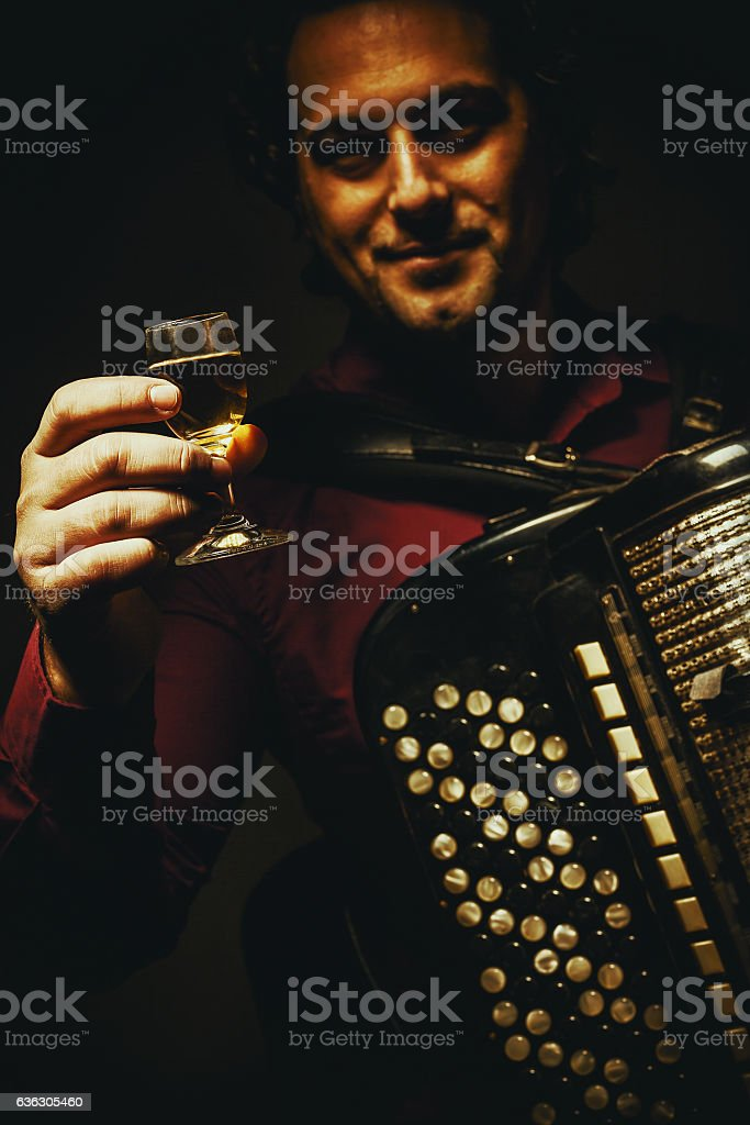The chromatic accordion player and a glass of alcoholic beverage. stock photo