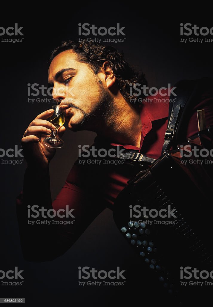 The chromatic accordion player drinking a spirit drink. stock photo
