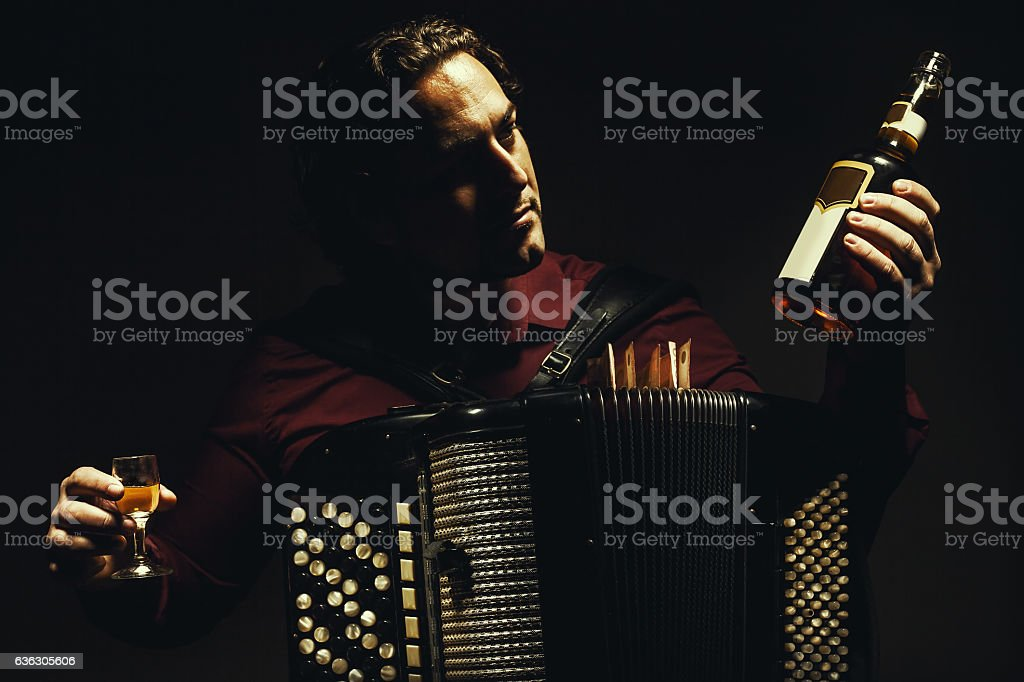 The chromatic accordion player with a spirit drink. stock photo