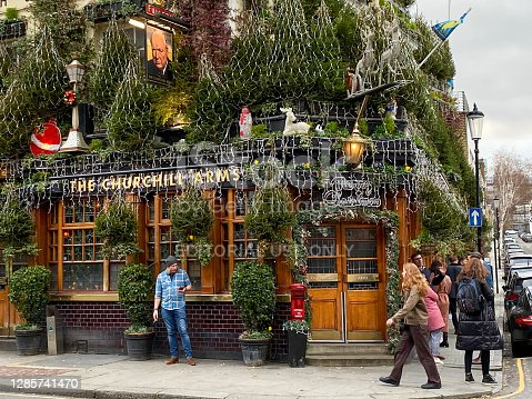 The Churchill Arms in Kensington, London. This pub was built in 1750 and was once a haunt of Winston Churchill's grandparents. There is Churchill memorabilia inside. Cars and people can be seen outside.