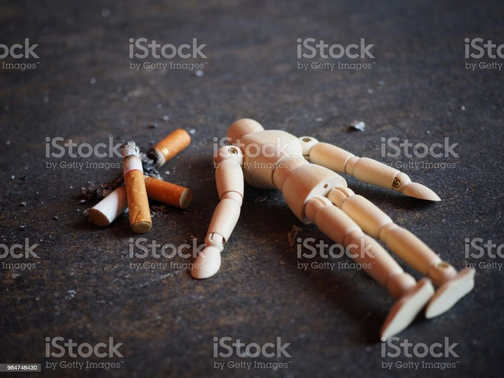 The cigarette burns out and the dummy is dumped like a dead smoker. In the concept of stop smoking 31 May World No Tobacco Day royalty-free stock photo